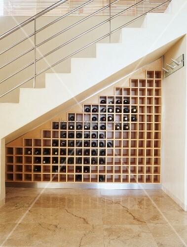 Stauraum für Weinflaschen unter einer Treppe mit Metallgeländer