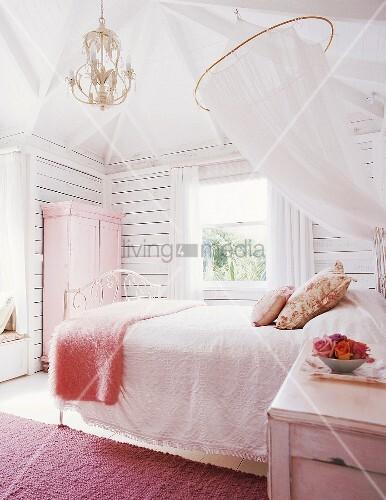 feminines schlafzimmer mit doppelbett unter moskitonetz und rosa kleiderschrank an holzwand. Black Bedroom Furniture Sets. Home Design Ideas