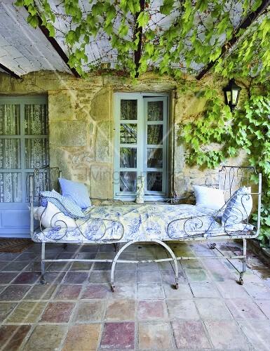 kunstvolles metallbett im shabby stil auf einer berdachten terrasse mit rankendem wein und. Black Bedroom Furniture Sets. Home Design Ideas