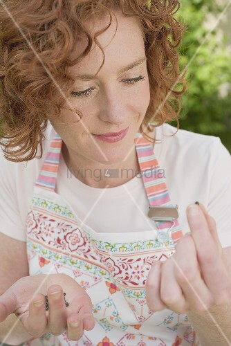 Junge Frau betrachtet Blumensamen