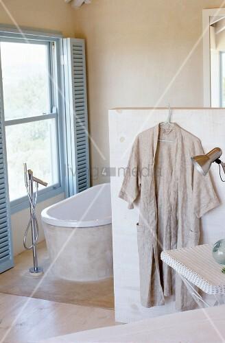 badezimmer in beige mit badewanne unter fenster mit blauen sonnenschutz von innen bild kaufen. Black Bedroom Furniture Sets. Home Design Ideas