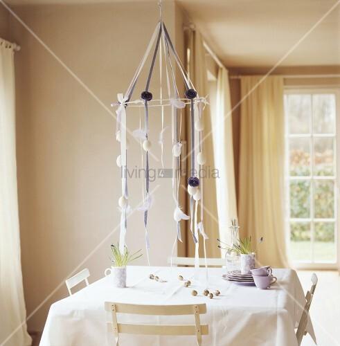 h ngende osterdekoration mit ostereiern ber quadratischem tisch mit weisser tischdecke bild. Black Bedroom Furniture Sets. Home Design Ideas