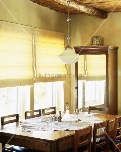alter holztisch mit st hlen und ein spiegelschrank im esszimmer eines rustikalen wohnhauses. Black Bedroom Furniture Sets. Home Design Ideas
