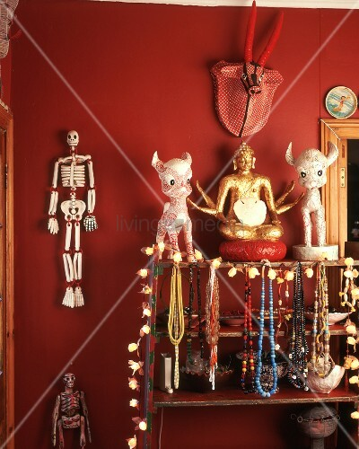 halsketten buddha figur deko figuren deko sklette auf regal an roter wand h ngend bild. Black Bedroom Furniture Sets. Home Design Ideas