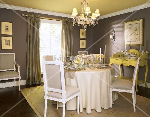 esszimmer mit festlich gedecktem rundem esstisch polsterst hlen kronleuchter bild kaufen. Black Bedroom Furniture Sets. Home Design Ideas