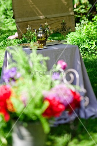 A bunch of flowers with a sliver jug and a cake on a table in the background