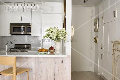 Moderne Einbauküche in Weiss mit Thresen neben kleinem Gang mit breiter Schrankwand