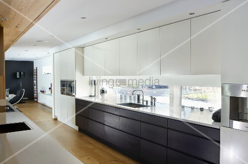 An open-plan designer kitchen - black and white fitted cupboards in front of a window bank