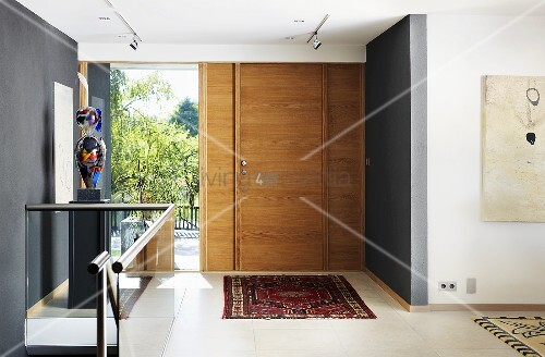A hallway in a house with a wooden door, a grey wall and a glass balustrade