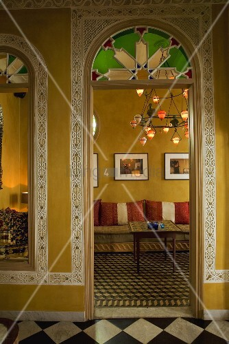 View through a rounded arch into a Moroccan living room with borders on the yellow walls and patterned tile floors