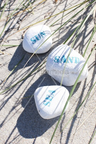 Beach holiday - stones with writing lying in the sand