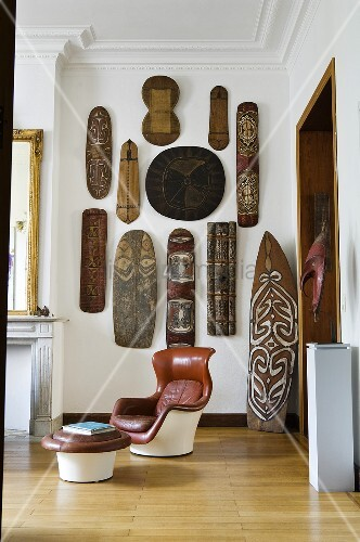 A living room in an old house - a leather chair with a foot stool with an African art collection on a wall