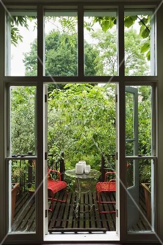 blick durch offenes fenster auf holzterrasse mit roten gartenst hlen und tisch bild kaufen. Black Bedroom Furniture Sets. Home Design Ideas