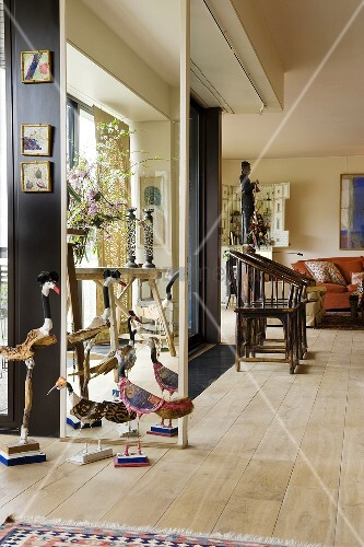 Funny bird ornaments in front of a floor-to-ceiling mirror and old wooden in a living room