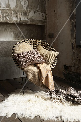 A cosy seating area in an attic - a bucket chair with a blanket and a cushion with a fur rug on the floor
