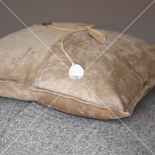 A necklace on a suede cushion