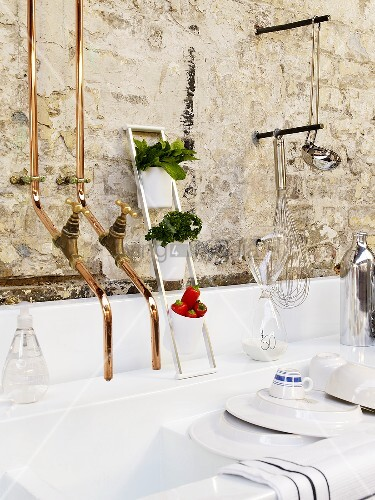 A white sink with brass taps with crockery and utensils on a white stone wall