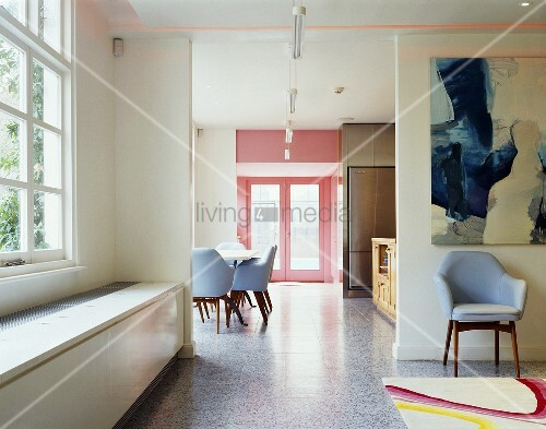 An open anteroom with a Bauhaus-style chair under a picture and a view of a dining area