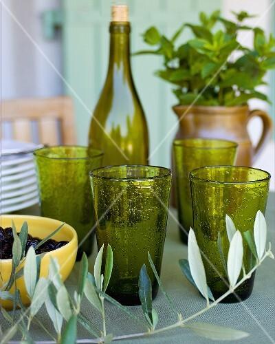Mediterranean still life - olive sprigs in front of green glasses
