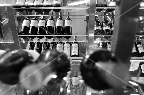 A black and white image of wine displayed on a glass shelf