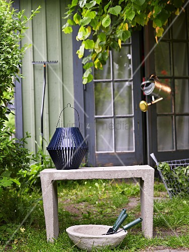 A blue lantern on a stone bench and bowl of garden tools in front of a garden shed