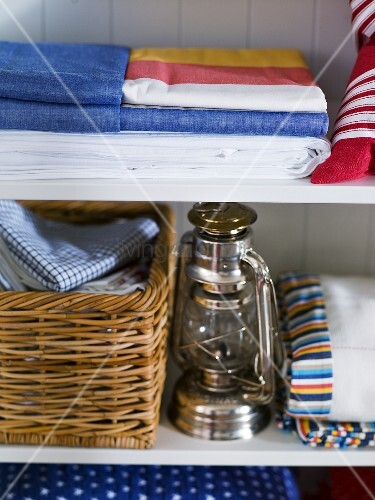 Bed linen and basket with laundry next to a kerosene lamp in white cupboard