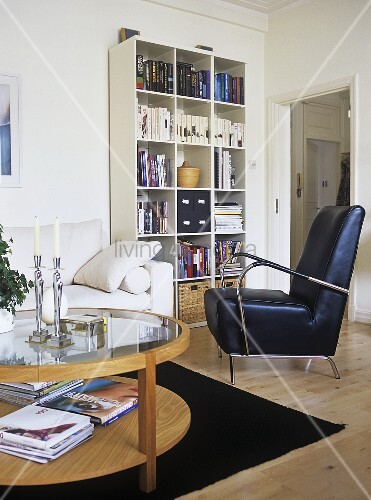 A modern, sitting room, bookcase, books, sofa, leather arm chair, rug, glass coffee table, candles, candlestick, plant,