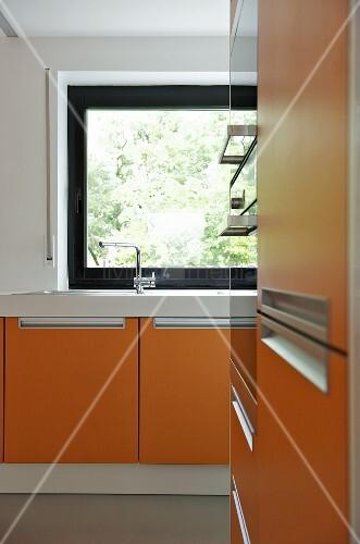moderne k che mit orangefarbenen fronten und fenster mit dunklem rahmen bild kaufen living4media. Black Bedroom Furniture Sets. Home Design Ideas