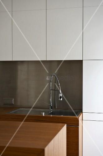 sp le mit armatur vor spritzschutz aus edelstahl und weisser einbauschrank bild kaufen. Black Bedroom Furniture Sets. Home Design Ideas