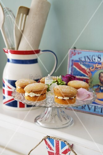 Fairy cakes on a glass cake stand and kitchen utensils in a Union Jack flag jug