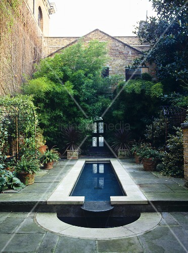 Exterior of brick house with paved patio around water feature.