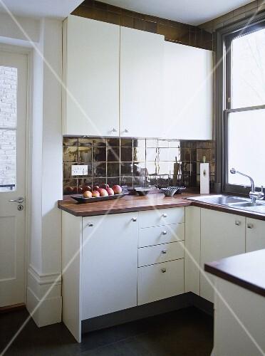 moderne k che mit wei en schr nken und dunklen fliesen an wand und boden bild kaufen. Black Bedroom Furniture Sets. Home Design Ideas