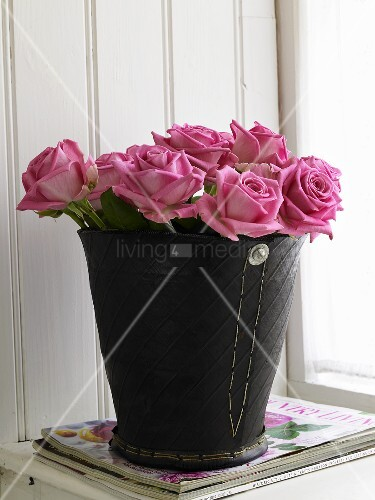 Pink roses in a black vase made from recycled tyre