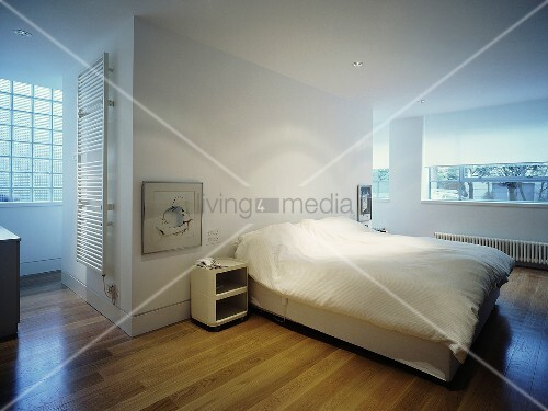 A white, open-plan bedroom with a double bed and parquet flooring