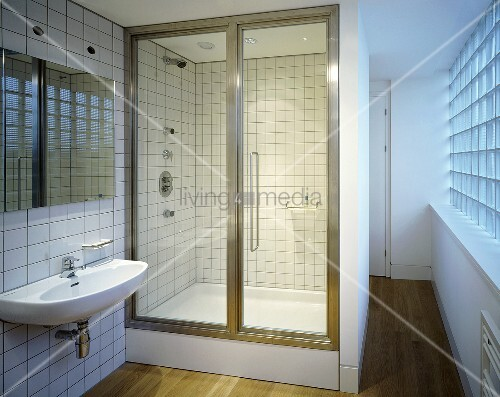A bathroom with a closed shower cubicle and a glass door