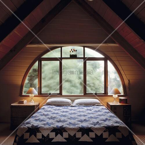 Ein Loft Schlafzimmer mit einem halbkreisförmigen Fenster und ...