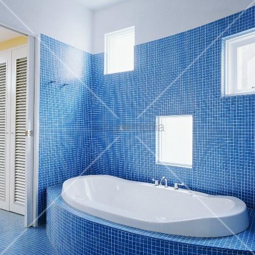 Ein modernes und mit blauer Mosaik gefliestes Badezimmer und eine ...