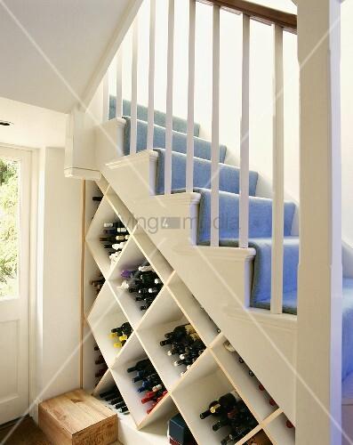 Weinflaschen in auf der Spitze stehendem Würfelregal unter weisser Holztreppe mit hellblauem Teppich