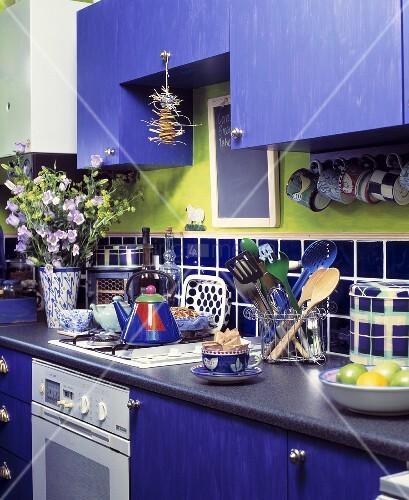 moderne k che mit blau lackierter schrankfront und gr nem wandstreifen ber blauen wandfliesen. Black Bedroom Furniture Sets. Home Design Ideas