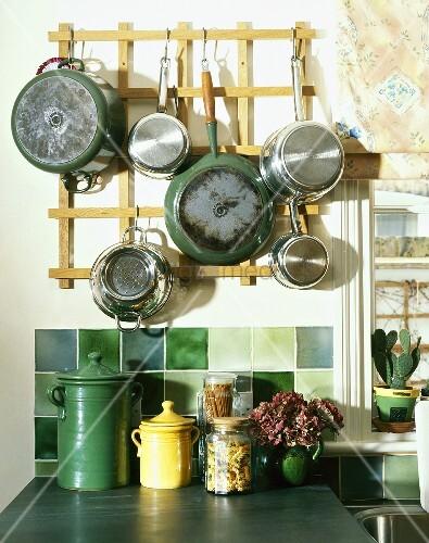 pfannen und t pfe am wandboard h ngend ber gr nen wandfliesen und keramikgef ssen auf ablage. Black Bedroom Furniture Sets. Home Design Ideas