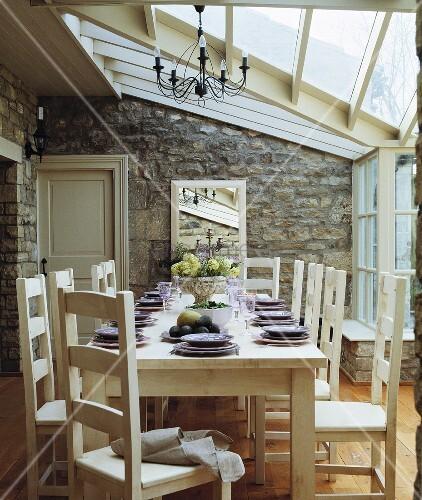 zeitgen ssisches esszimmer mit natursteinwand im wintergarten bild kaufen living4media. Black Bedroom Furniture Sets. Home Design Ideas