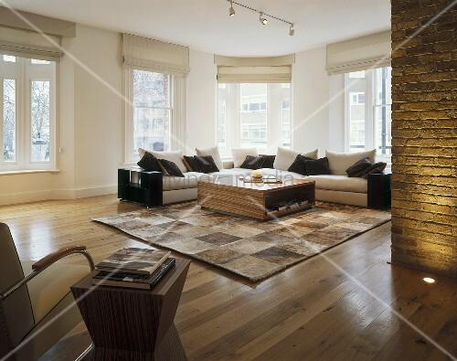 offener moderner wohnraum mit sofa bereck vor fenster und fellteppich im schachbrettmuster auf. Black Bedroom Furniture Sets. Home Design Ideas