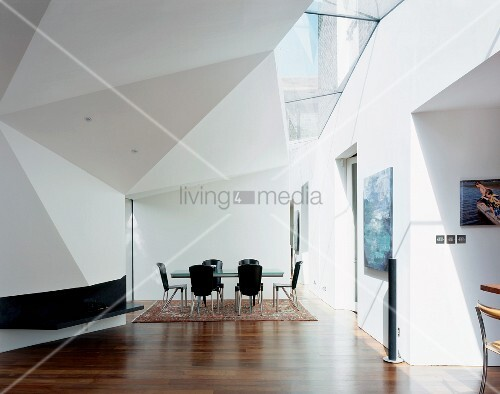 Futuristic living room with black dining chairs and table under a Geometrix ceiling